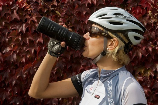 Bicycle racer in front of vine leaves drinking from a biking bottle : Stock Photo