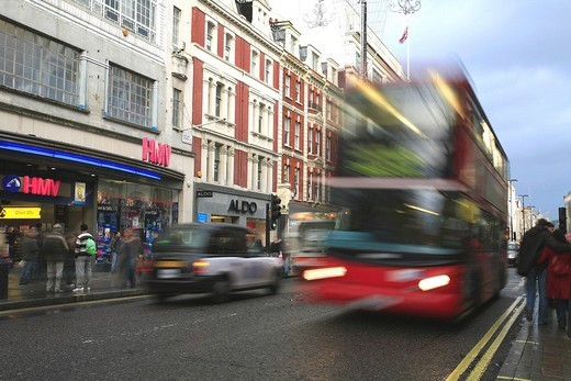In motion: Red London Bus running on Tottenham Court ROad, Oxford Circus, London, UK : Stock Photo