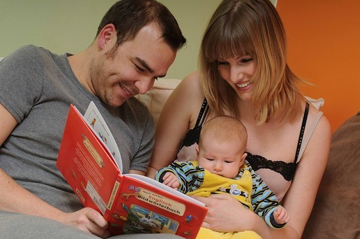 Father, mother and baby looking at an illustrated children´s dictionary : Stock Photo