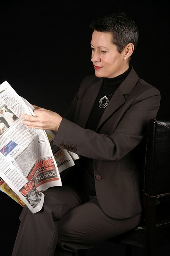 Stock Photo: 1848-95826 Woman reading newspaper