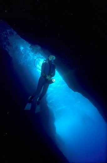 Diver is swimming in a big cave, Mediterranean Sea. : Stock Photo