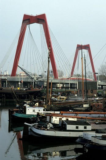 Traditional ships in the port of Oude, part of the Rotterdam Port Museum, in front of the red Willemsbrug bridge, Rotterdam, province of South Holland, Zuid Holland, the Netherlands, Europe : Stock Photo