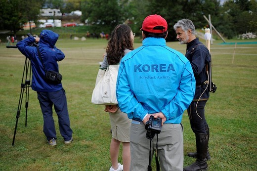 Stock Photo: 1848-99115 A Korean team member watching a Korean TV interview with a British participant, open Eocha European championship 09, mounted archery, with steppe riders from all over the world, Trossenfurt, Franconia, Bavaria, Germany, Europe