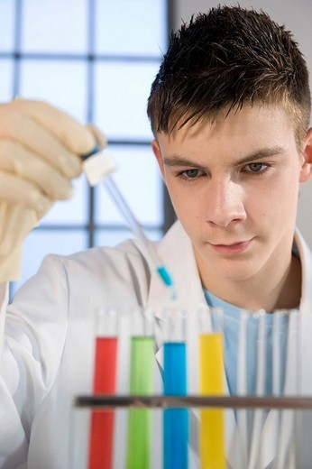Teenage boy in a laboratory, working with test tubes : Stock Photo