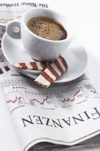 Cup of espresso sitting on top of newspaper, financial section : Stock Photo