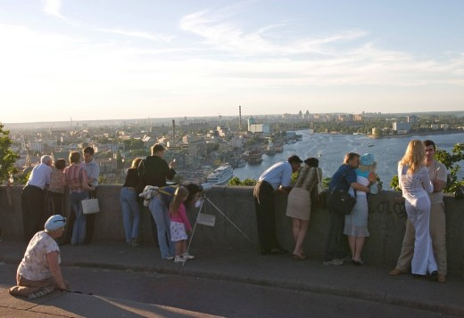 Stock Photo: 1848R-278417 Ukraine Kiev view to a part of the city with visitors young couples with view to Podil landing place ships river Dnepr trees buildings city view at the river Dnepr sunset 2004