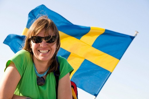 Stock Photo: 1848R-278989 Laughing young woman in front of Swedish flag