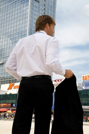 Stock Photo: 1848R-279687 Young businessman on the street holding jacket