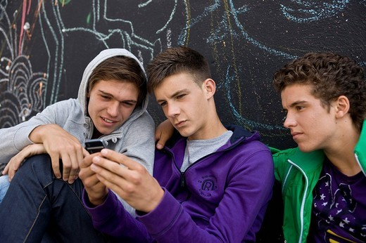 Three boys sitting with their backs against a wall, sending text messages, cool : Stock Photo
