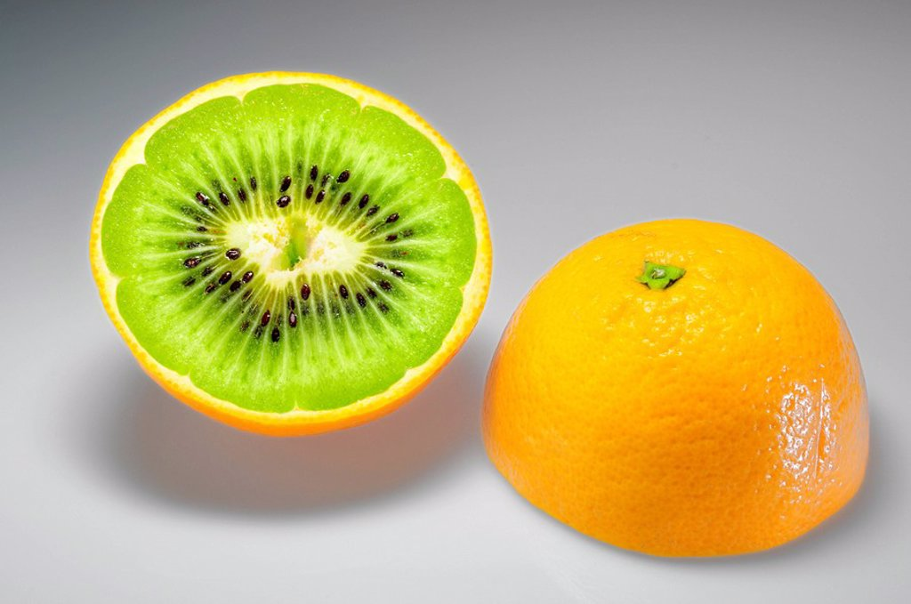 Orange filled with a Kiwi, symbolic image for genetic engineering : Stock Photo