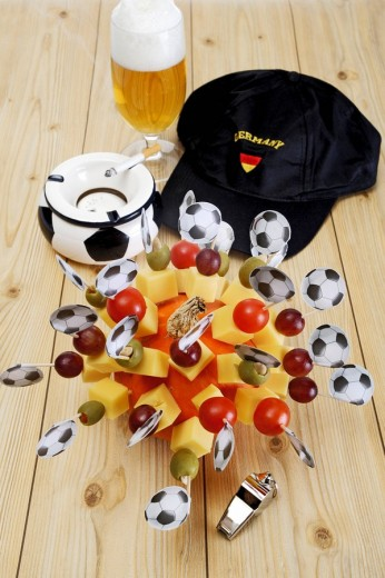 Stock Photo: 1848R-283822 Cheese snacks, finger food, football flags, football memorabilia, ashtray, football cap, whistle and a glass of beer