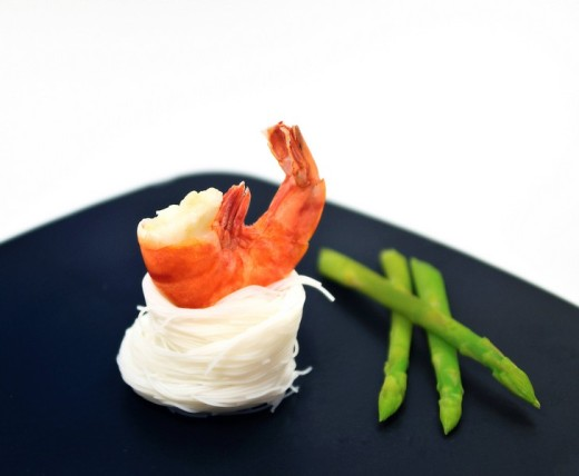 Scampi on a bed of rice noodles and Thai asparagus : Stock Photo