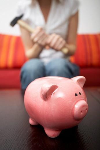 Stock Photo: 1848R-284987 Piggy bank, woman holding a hammer