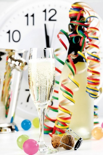 Stock Photo: 1848R-285905 Glass and bottle of champagne with paper streamers, clock showing shortly before 12:00