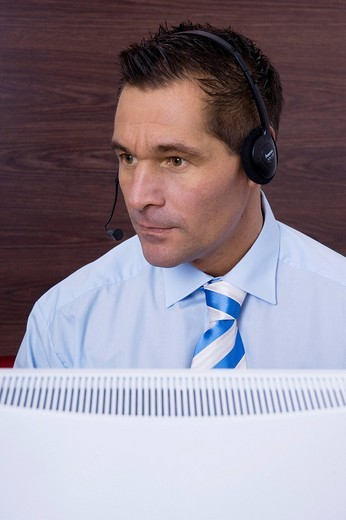 Stock Photo: 1848R-286131 Man wearing a headset in front of his computer