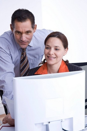 Businessman and businesswoman at a meeting in front of a laptop : Stock Photo