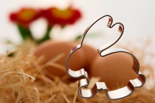 Stock Photo: 1848R-287243 Bunny cookie cutter in front of eggs in a wood wool nest
