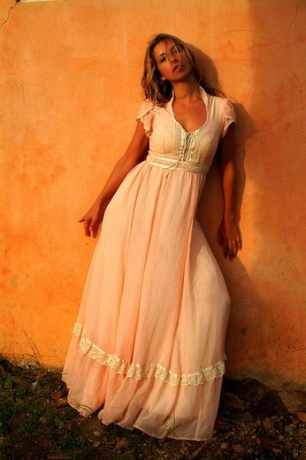 Young woman wearing long, rose-coloured princess dress standing in front of a terracotta house facade : Stock Photo