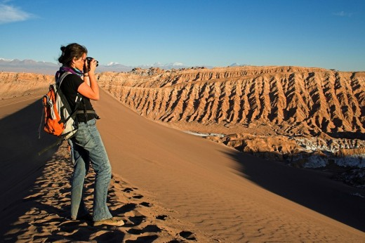 Woman with a camera on a sand dune in the Moon Valley Valle de la luna, Atacama desert, northern Chile, South America : Stock Photo