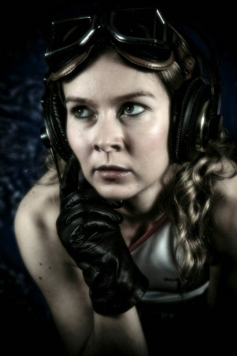 Stock Photo: 1848R-289329 Young woman with headphones, motorcycle goggles and gloves