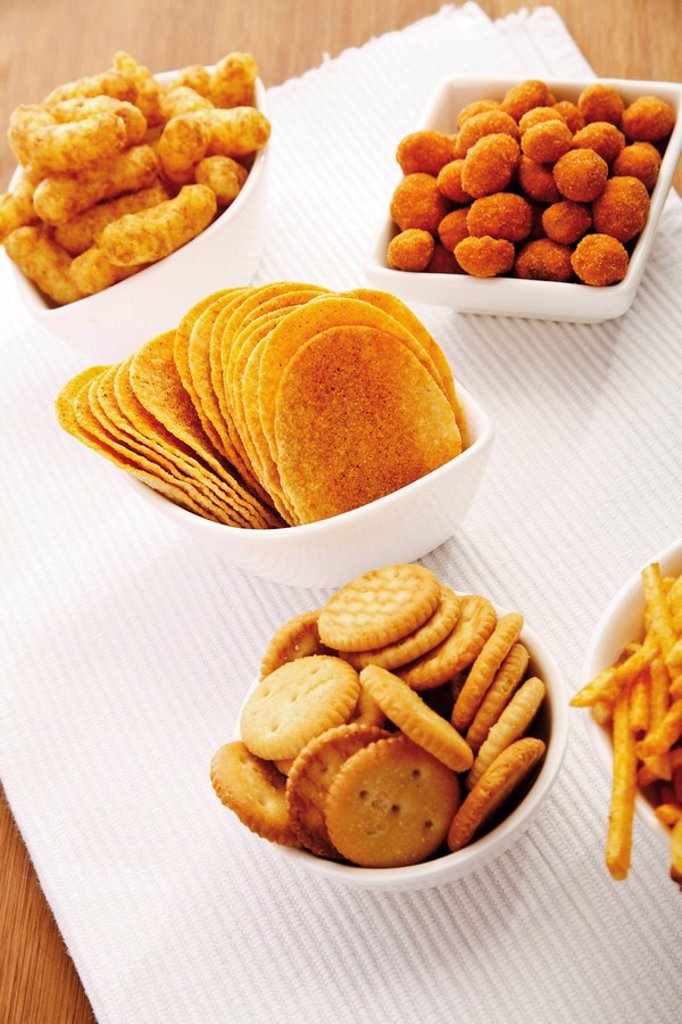 Stock Photo: 1848R-291314 Various spiced snacks in bowls on a table, crisps, peanut flips, potato sticks and salted cookies