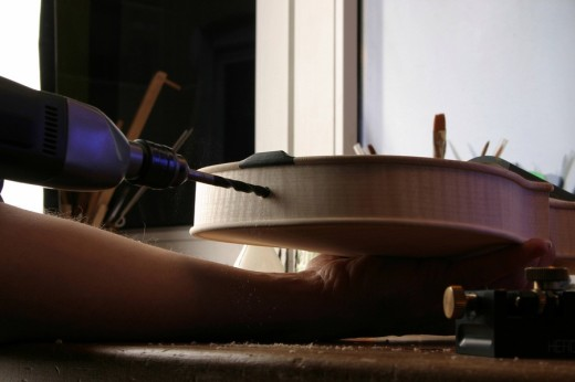 Stock Photo: 1848R-292092 Violin-maker luthier drilling a hole for the screw holding the tailpiece in place