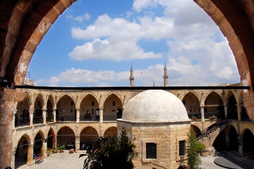 Arches of the old caravan rest Bueyuek Han with domed tower in the yard Lefkosa Nicosia North Cyprus : Stock Photo