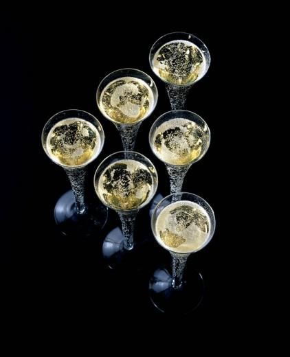 Six flutes of champagne on black surface : Stock Photo