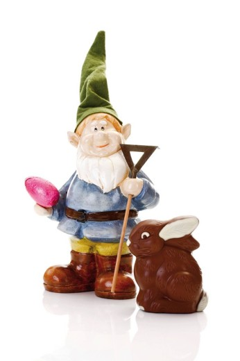Stock Photo: 1848R-295558 Garden gnome with a rake and an easter egg standing in front of a chocolate easter bunny