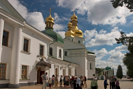 Ukraine Kiev the monastery of cave Kyjevo Pecers´ka Lavra view to church of crucify in ukrain barock style and chapel of grave from O Bezak 1860 pilgrims believers tourists in front of the church blue sky and clouds 2004 : Stock Photo