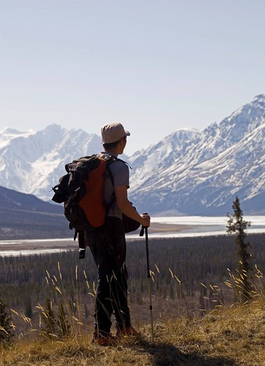 Stock Photo: 1848R-299014 Hiker enjoying the view at the Slims River Valley and Kaskawulsh Glacier, Saint Elias Mountains, Kluane National Park and Reserve, Yukon Territory, Canada, North America, North America