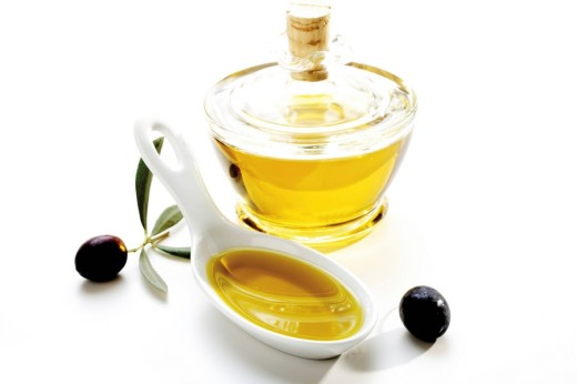 Porcelain spoon with olive oil, olives and olive oil bottle : Stock Photo