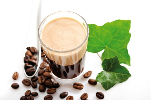 Glass of Irish cream coffee, coffee beans and ivy leaf : Stock Photo