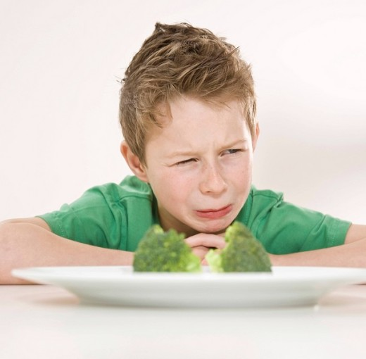 Boy sitting in front of a plate of broccoli with a disgusted look on his face : Stock Photo