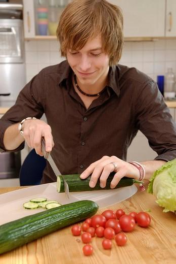 Man cuts cucumbers : Stock Photo