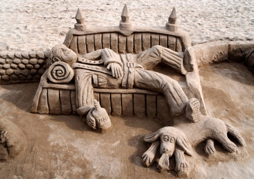 Sand sculpture of a tramp with a dog lying on a bench : Stock Photo