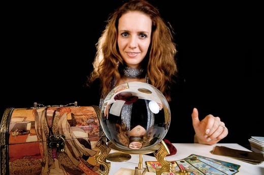 Fortune teller in front of a crystal ball with cards : Stock Photo