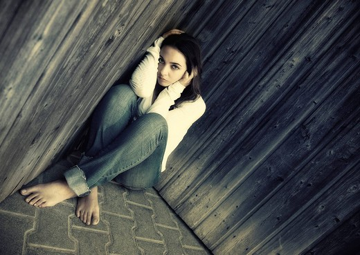 Young sad woman in jeans is sitting in a corner with her back to the wall : Stock Photo