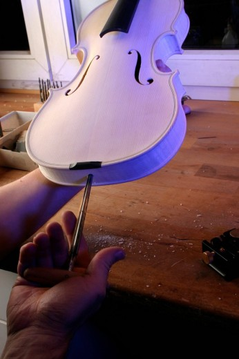 Violin-maker luthier drilling a hole for the screw holding the tailpiece in place : Stock Photo