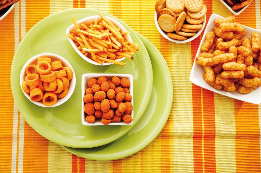 Various spiced snacks in bowls, crisps, peanut flips, potato sticks, roasted peanuts, pretzel sticks and potato rings : Stock Photo