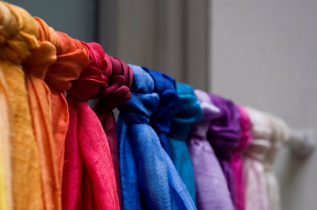 Knotted cotton scarfs on a curtain-pole : Stock Photo