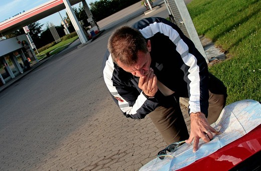 Car driver searching for the destination the conventional way, Malente, Schleswig-Holstein, Germany : Stock Photo