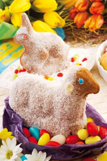 Stock Photo: 1848R-306790 Easter bunny and lamb made of dough, sprinkled with icing sugar sitting on colourful eggs