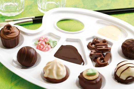 Filled chocolates on a colour palette : Stock Photo