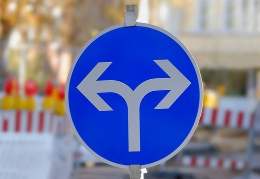Traffic sign with two directional arrows in order to detour a road construction site : Stock Photo