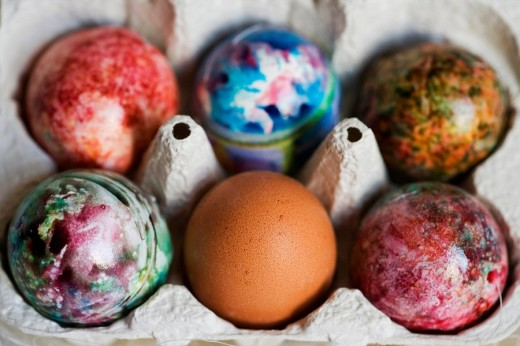 Five painted, coloured Easter eggs and one plain brown egg in an egg carton : Stock Photo