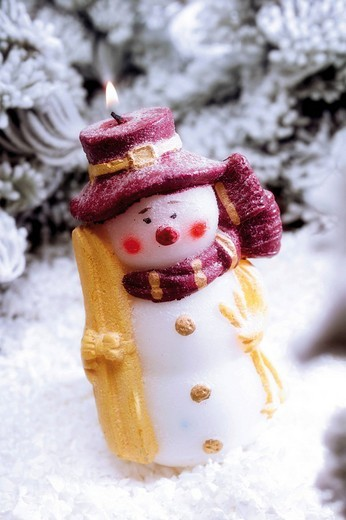Snowman candle in a snowy forest : Stock Photo
