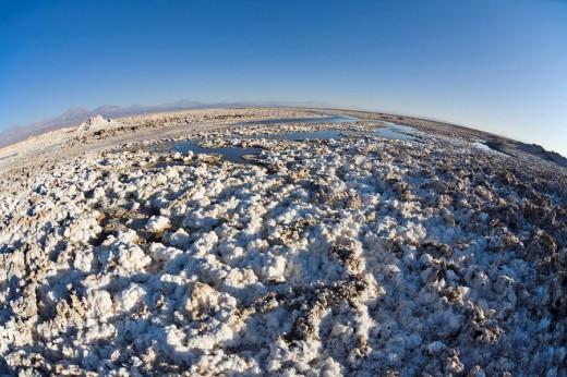 Salt formations covering the ground of the Reserva Nacional los Flamencos at the Salar de Atacama salt flats, Región de Antofagasta, Chile, South America : Stock Photo