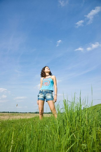 Young girl standing on a meadow and enjoying the sunshine : Stock Photo