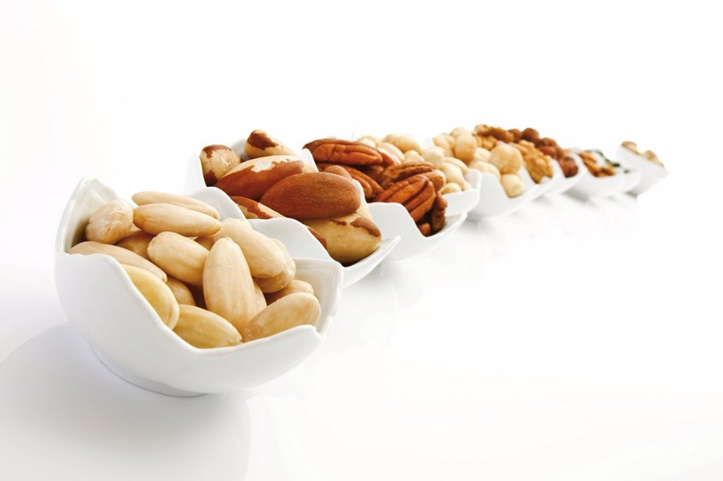 Stock Photo: 1848R-312200 Kernels of assorted nuts in porcelain bowls